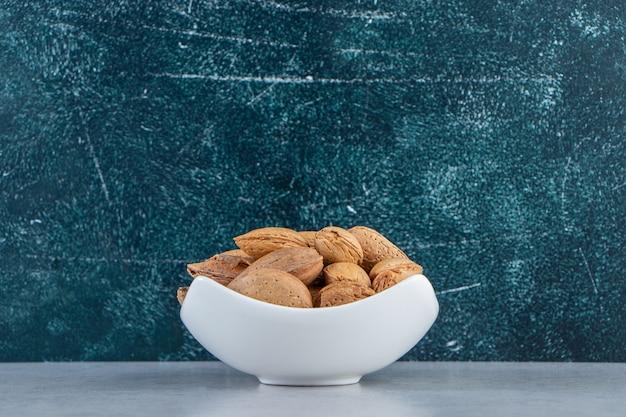 Biała miska pełna łuskanych migdałów na kamiennym tle.