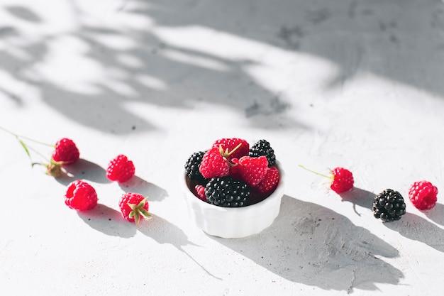 Biała miska pełna malin, jeżyny na szarym betonowym stole z liśćmi, cień gałęzi drzew. koncepcja zdrowego odżywiania. eko, biorolnictwo. świeże, smaczne jagody na szarym tle. zdjęcie wysokiej jakości