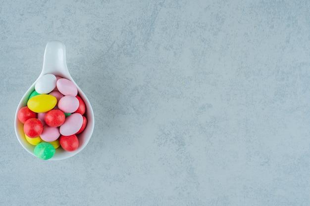 Biała miska pełna okrągłych słodkich kolorowych cukierków na białej powierzchni