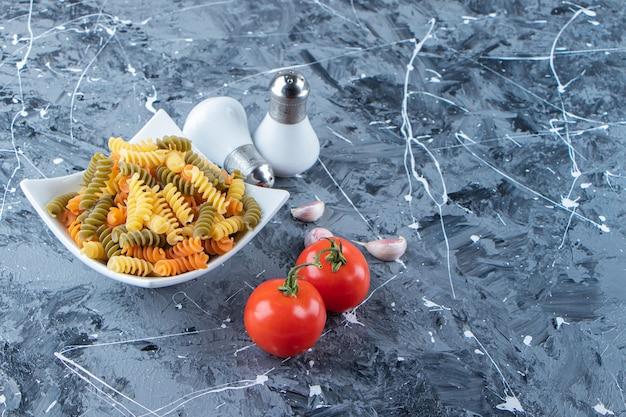 Biała miska pełna różnokolorowych makaronów z warzywami i przyprawami na marmurowej powierzchni.
