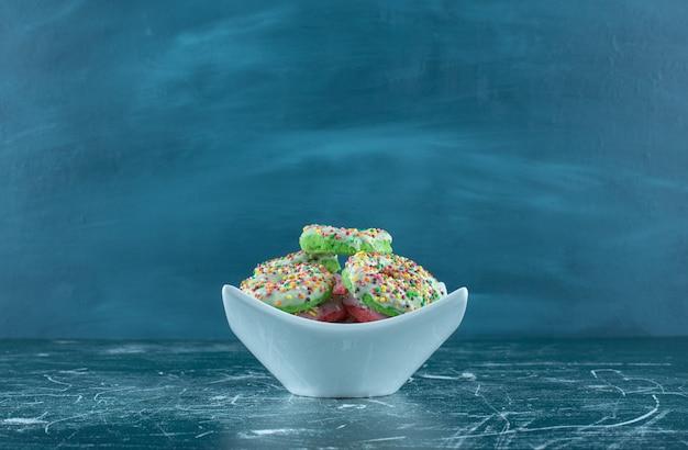 Biała miska pełna słodkich pączków na niebieskim tle. wysokiej jakości zdjęcie
