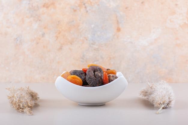 Biała miska pełna suszonych owoców na białym tle. zdjęcie wysokiej jakości