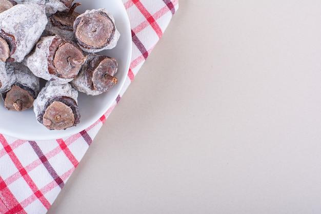 Biała miska pełna suszonych persimmons na białym tle. zdjęcie wysokiej jakości