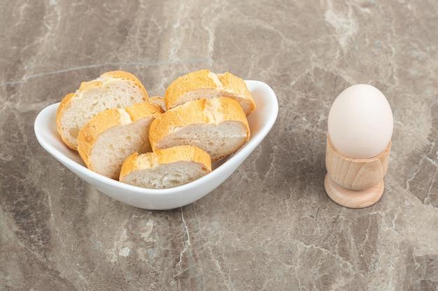 Biała miska pełna świeżego krojonego chleba i jajka na marmurowej powierzchni.