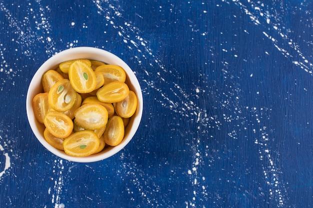 Biała miska pokrojonych w plasterki owoców kumkwatu na powierzchni marmuru.
