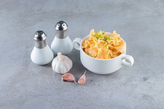 Biała miska pysznego makaronu z czosnkiem i solą na kamiennym tle.