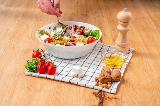 Biała miska sałatki lodowej i rukoli o intensywnym zielono-fioletowym kolorze z mieszanką bardzo zdrowych składników do diety takich jak orzechy, ser, wiśnie, pomidory, oliwki, marchewka i kukurydza.