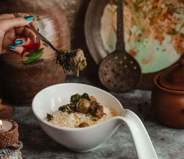 Biała miska tradycyjnego govurma plov z suszonymi owocami i kasztanami