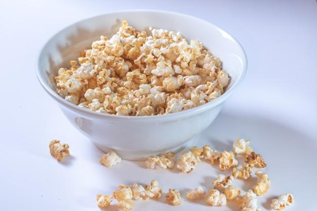 Biała miska z słodkim popcornem na białym tle