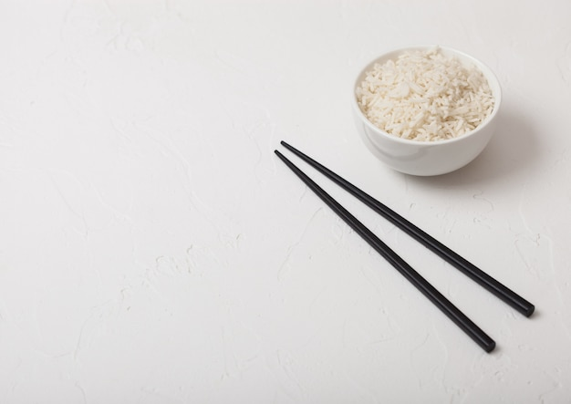 Biała miska z ugotowanym organicznym ryżem jaśminowym basmati z czarnymi pałeczkami