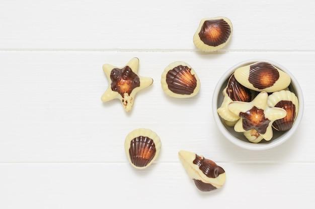 Biała miska ze słodyczami w postaci muszelek na białym rustykalnym stole. słodycz mlecznej czekolady. widok z góry. leżał na płasko.