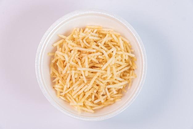 Biała miska ze słomką ziemniaczaną na białym tle