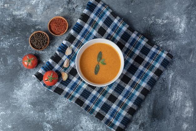 Biała miska zupy z soczewicy z warzywami na pięknym obrusie.