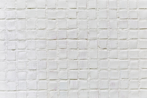 Biała mozaika na ścianie domu, na zewnątrz. przestrzenie i tekstury. miejsce na tekst. zbliżenie.