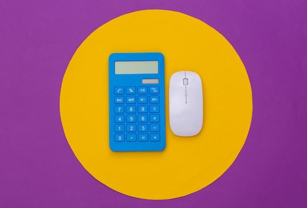 Biała mysz komputerowa i kalkulator na fioletowym tle z żółtym kółkiem. koncepcyjne studio strzał. minimalizm. widok z góry