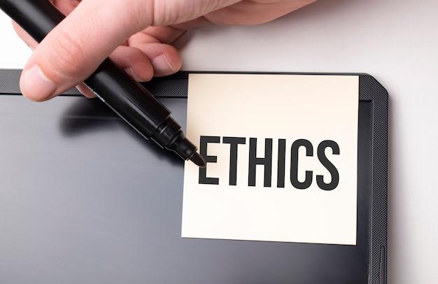 Biała naklejka na monitorze w biurze z napisem etyka i ręką z markerem