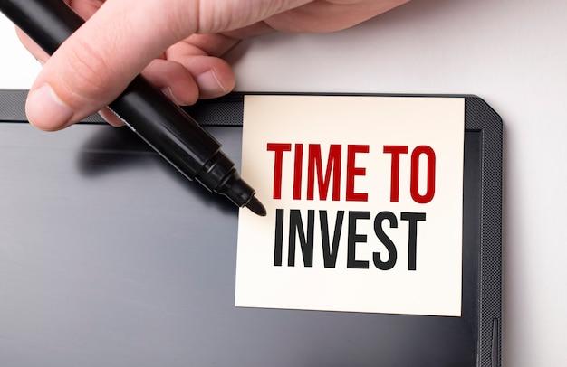 Biała naklejka na monitorze w biurze z tekstem czas na inwestycje i rękę z markerem