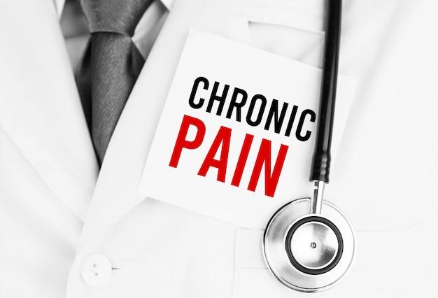 Biała naklejka z napisem chronic pain leżąca na fartuchu medycznym ze stetoskopem
