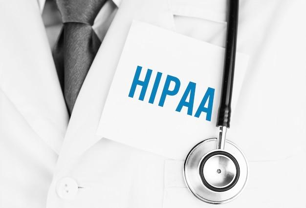 Biała naklejka z napisem hipaa leżąca na fartuchu medycznym ze stetoskopem