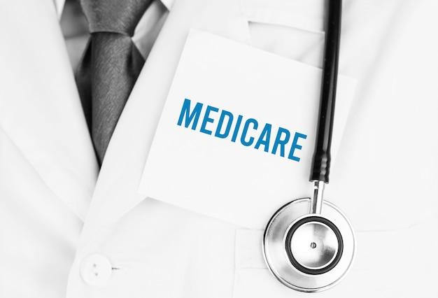 Biała naklejka z napisem medicare leżąca na fartuchu lekarskim ze stetoskopem