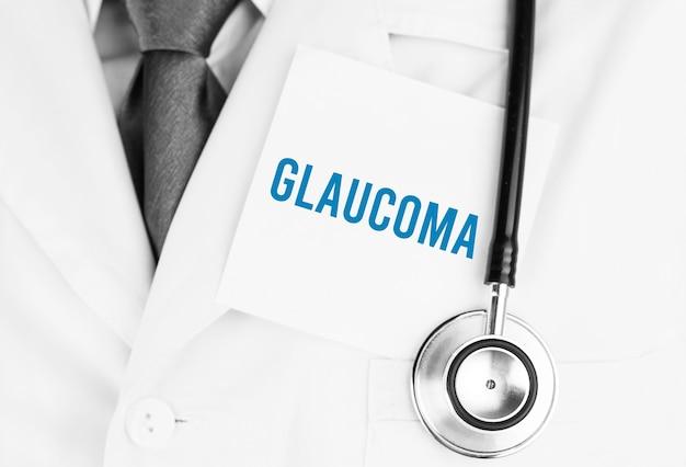 Biała naklejka z tekstem jaskra leżąca na fartuchu medycznym ze stetoskopem