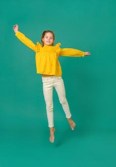 Biała nastolatka 10 lat w żółtej bluzce i białych spodniach skacze na zielonej powierzchni