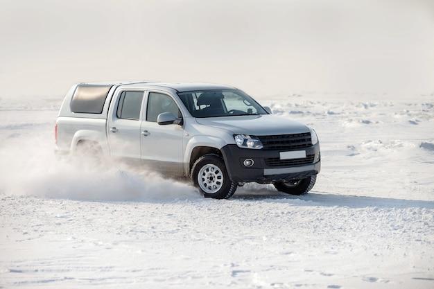 Biała niemiecka ciężarówka jadąca po śniegu i płatki śniegu lecące z kół