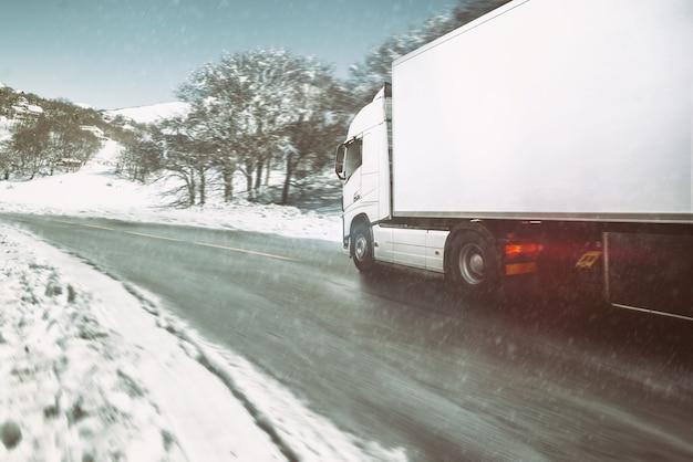 Biała nowoczesna ciężarówka porusza się szybko zimą po drodze ze śniegiem