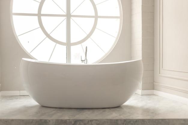 Biała, nowoczesna wanna podłogowa z okrągłym oknem i pastelowymi ścianami ze sztukaterią