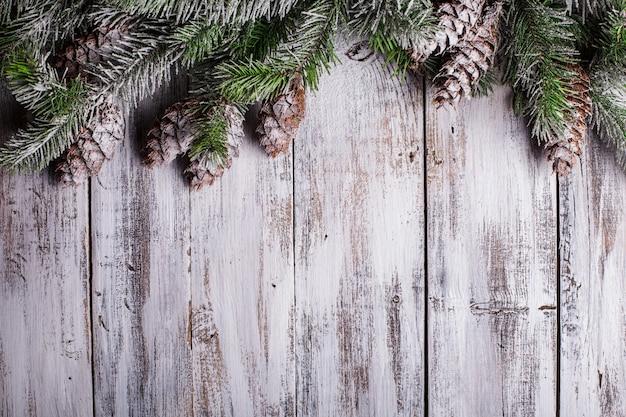 Biała odrapana bożonarodzeniowa granica z pokrytymi śniegiem szyszkami