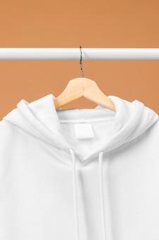 Biała odzież na wieszaku z widokiem z przodu etykiety