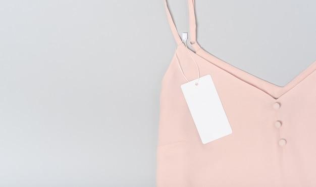 Biała odzież tag, etykieta pusty szablon makieta. na bawełnianej różowej bluzce premium na szarym tle