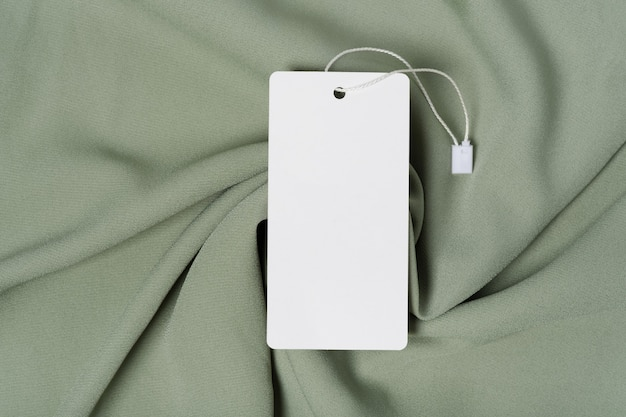 Biała odzież tag, etykieta pusty szablon makieta. na wysokiej jakości bawełnianej tkaninie w kolorze zielonym khaki
