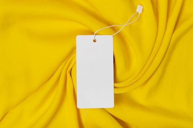 Biała odzież tag, etykieta pusty szablon makieta. najwyższej jakości tkanina bawełniana z żółtej tkaniny