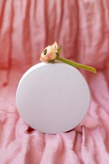 Biała okrągła figura i suszony kwiat na różowej powierzchni tkaniny