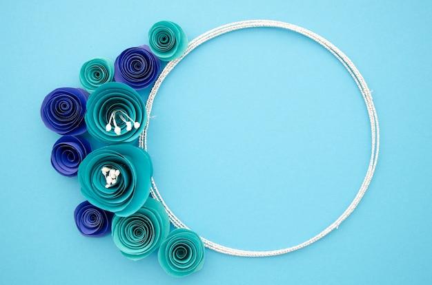 Biała ozdobna ramka z niebieskimi papierowymi kwiatami