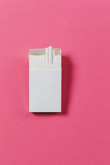 Biała paczka papierosów na różowym tle róż