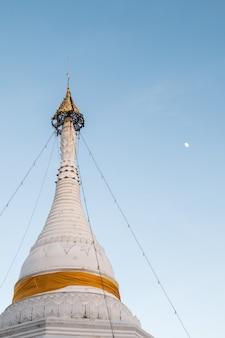 Biała pagoda ze złotym parasolem na szczycie.