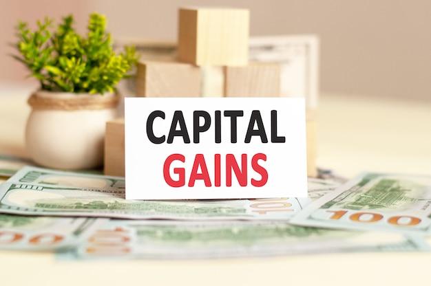 Biała papierowa karta z tekstem zysków kapitałowych, na tle papierowych pieniędzy. pomysł na biznes