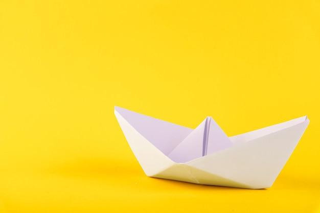 Biała papierowa łódź na żółtym tle