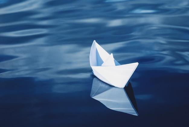 Biała papierowa łódź unosząca się w błękitnym morzu