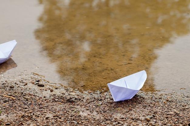Biała papierowa łódź zabawka na błękitnej wodzie w pobliżu brzegu.