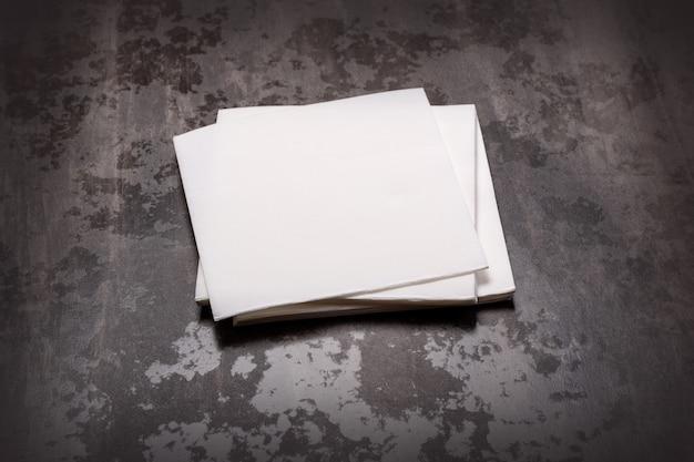 Biała papierowa serwetka na szarym tle kamiennego stołu.