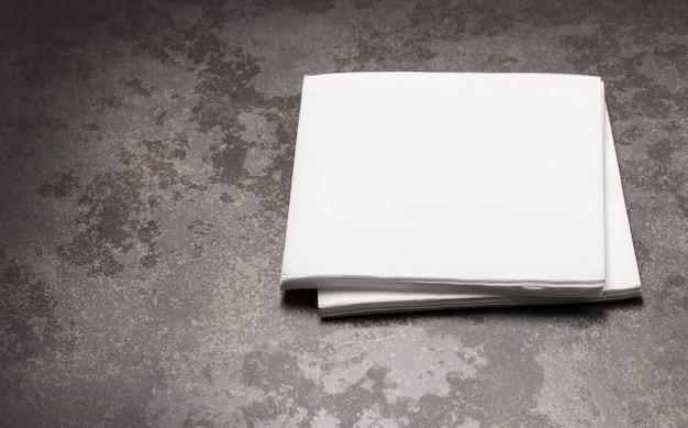 Biała papierowa serwetka na tle kamiennego stołu.