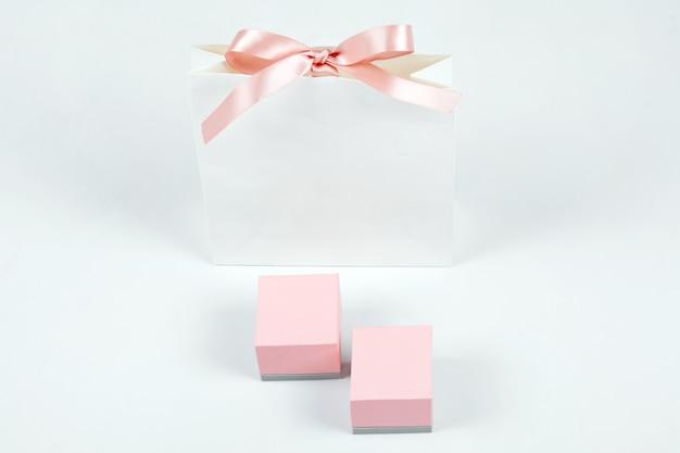 Biała papierowa torba na zakupy z kokardą i różowymi pudełkami na jasnym tle. koncepcja zakupy, sprzedaż, niespodzianka lub prezent.
