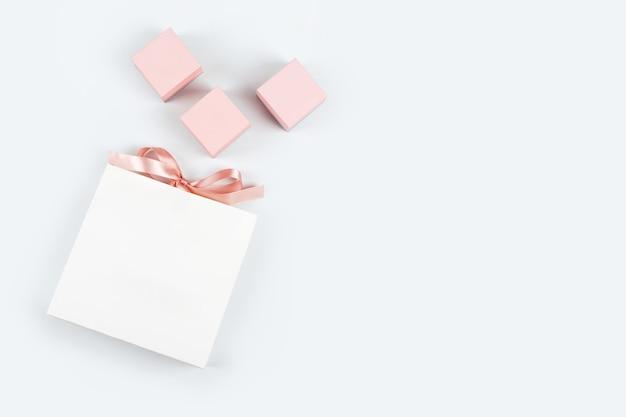 Biała papierowa torba na zakupy z kokardką i trzema różowymi pudełeczkami na jasnym tle. zakupy, sprzedaż, temat na prezent.