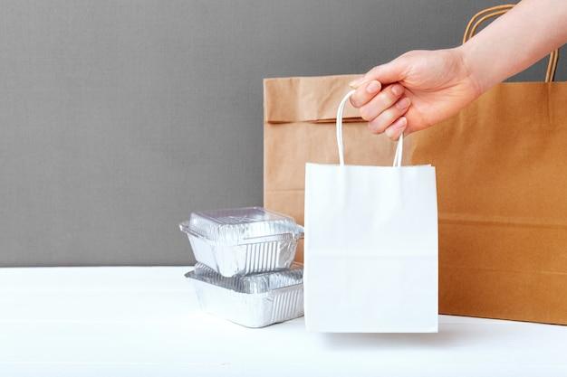 Biała papierowa torba rzemieślnicza w kobiecej dłoni. pojemniki foliowe na żywność i opakowania papierowe
