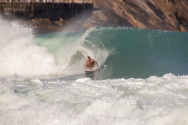 Biała piana fali na plaży leblon z defocused surfer w tle w rio de janeiro