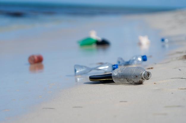 Biała piaszczysta plaża z plastikową koncepcją śmieci i wpływu na środowisko