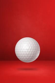 Biała piłeczka golfowa na białym tle na czerwonym studio
